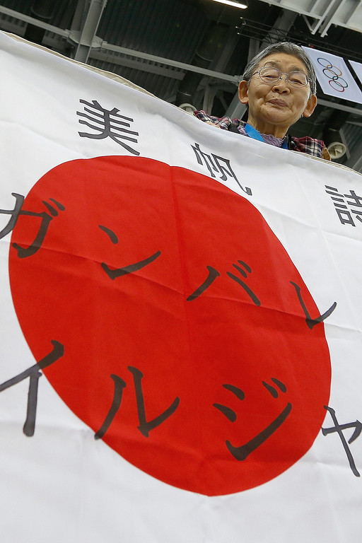 . A Japanese fan looks over a banner before the Sweden v. Japan women\'s ice hockey game at Shayba Arena during the 2014 Winter Olympics, Sunday, Feb. 9, 2014, in Sochi, Russia. (AP Photo/Petr David Josek)