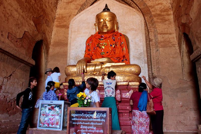 Putting gold leaf on a Buddha image
