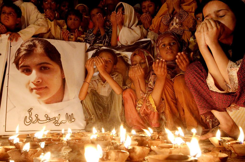 """. Pakistani children pray for the recovery of 14-year-old schoolgirl Malala Yousufzai, who was shot on Tuesday by the Taliban for speaking out in support of education for women, during a candlelight vigil in Karachi, Pakistan, Friday, Oct. 12, 2012. A Pakistani military spokesman says Yousufzai is in \""""satisfactory\"""" condition but cautions that the next few days will be critical. Writing reads on the poster left, \""""Malala Yousufzai.\""""  (AP Photo/Shakil Adil)"""