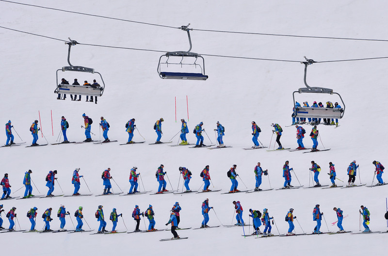 . Volunteers flatten the snow prior to the start of the Men\'s Alpine Skiing Super Combined Slalom at the Rosa Khutor Alpine Center during the Sochi Winter Olympics on February 14, 2014.  (DIMITAR DILKOFF/AFP/Getty Images)