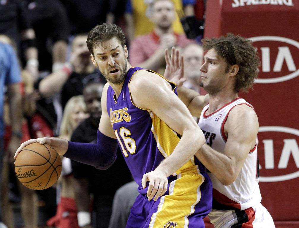 . Los Angeles Lakers center Pau Gasol, from Spain, left, backs in on Portland Trail Blazers center Robin Lopez during the second half of an NBA basketball game in Portland, Ore., Monday, March 3, 2014.  Gasol topped the Lakers in scoring with 22 points as they won 107-106. (AP Photo/Don Ryan)