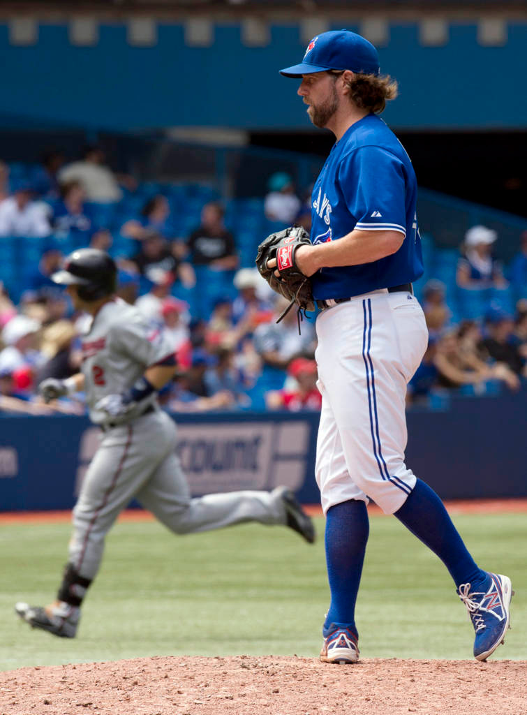 . Toronto Blue Jays starting pitcher R.A. Dickey stands on the mound as Minnesota Twins\' Brian Dozier rounds the bases on a three-run home run during the seventh inning. (AP Photo/The Canadian Press, Frank Gunn)