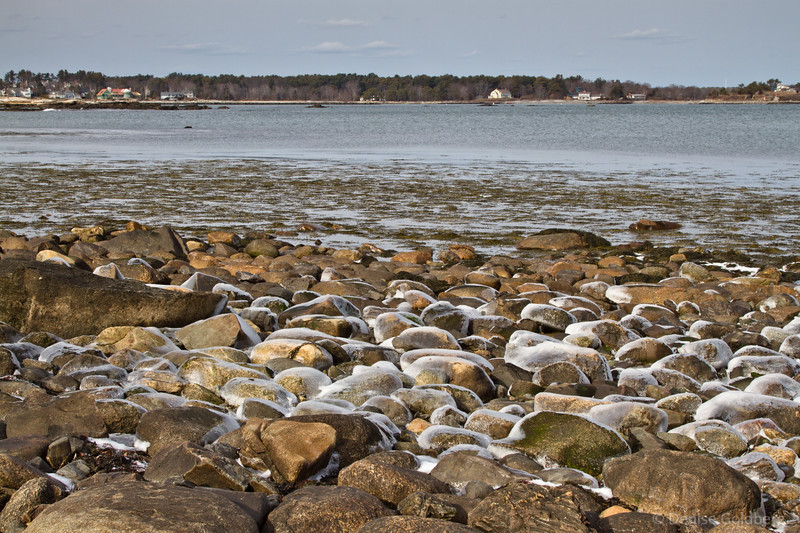 rounded rocks wearing a thin layer of ice