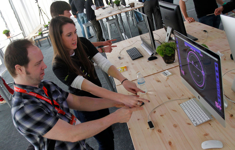 . LeapMotion marketing manager Julia Parson assists Justin Davis in using her company\'s 3D motion control during the SXSW Interactive Festival, Saturday, March 9, 2013 in Austin, Texas. The flash drive-sized device utilizes only hand movement to control a computer.  (AP Photo/Jack Plunkett)