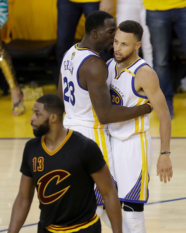. Golden State Warriors forward Draymond Green (23) talks with guard Stephen Curry (30) behind Cleveland Cavaliers center Tristan Thompson (13) during the first half of Game 5 of basketball\'s NBA Finals in Oakland, Calif., Monday, June 12, 2017. (AP Photo/Marcio Jose Sanchez)