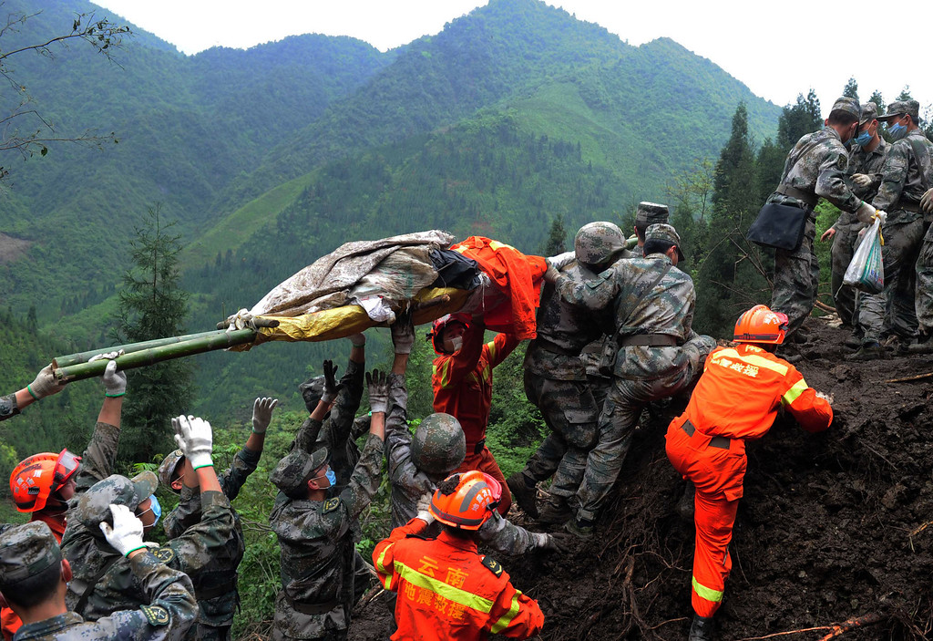 . This photo taken on April 25, 2013 shows rescuers carrying a victim\'s body in Taiping township in Lushan county of Yaan, southwest China\'s Sichuan province.  Tens of thousands of homeless survivors of China\'s devastating quake are living in makeshift tents or on the streets, facing shortages of food and supplies as well as an uncertain future.  AFP/Getty Images