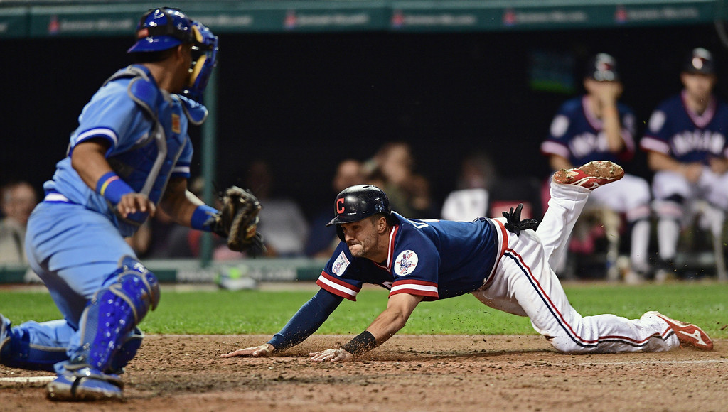 . Cleveland Indians\' Lonnie Chisenhall slides into home as Kansas City Royals\' Salvador Perez looks on in the sixth inning of a baseball game Saturday, June 4, 2016, in Cleveland, Ohio. (AP Photo/David Dermer)