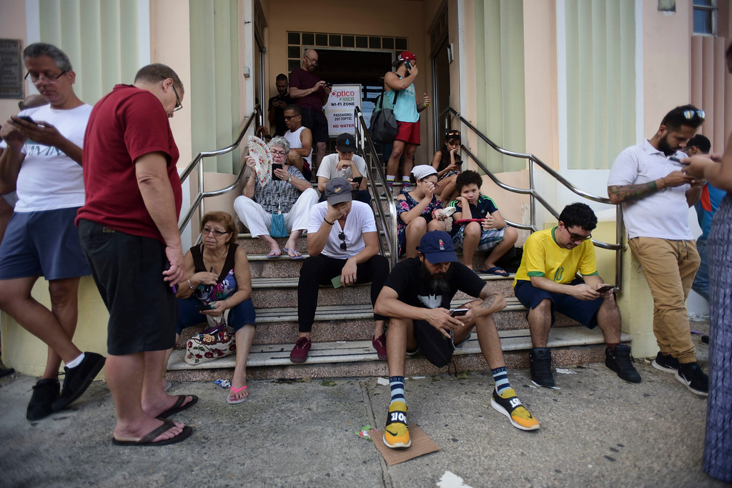 . People congregate at a wifi hotspot in the aftermath of Hurricane Maria with many cellphone towers down in San Juan, Puerto Rico, Sunday, Sept. 24, 2017. (AP Photo/Carlos Giusti)