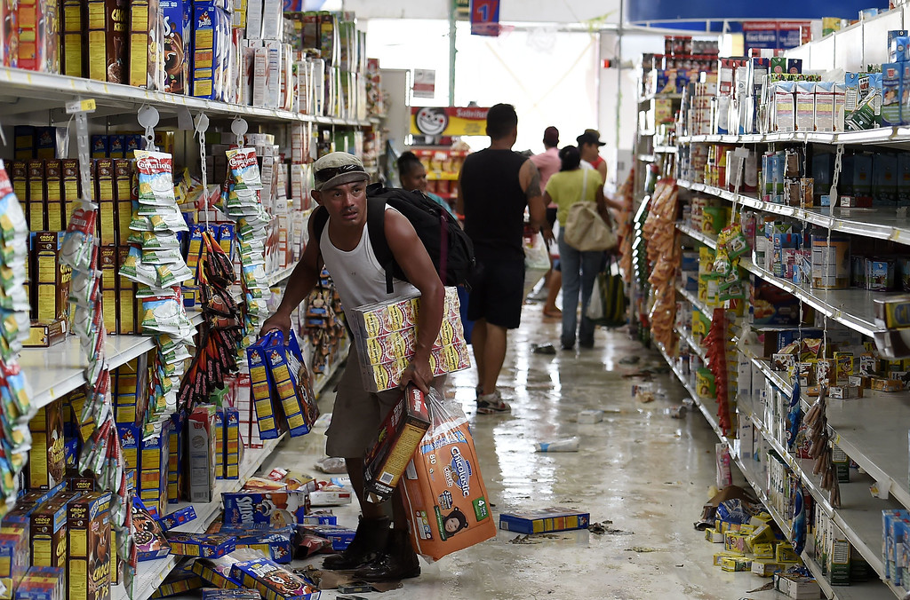 . People loot a supermarket in San Jose del Cabo, on September 15, 2014 after hurricane Odile knocked down trees and power lines in Mexico\'s Baja California peninsula. Odile weakened to category two on the five-level Saffir-Simpson scale but still packed powerful winds of 175 kilometers (110 miles) per hour after crashing ashore overnight near Cabo San Lucas, according to the US National Hurricane Center. Some 24,000 foreign tourists and 6,000 Mexican beachgoers spent the night in hotels where conference rooms were transformed into shelters. AFP PHOTO/RONALDO SCHEMIDT/AFP/Getty Images