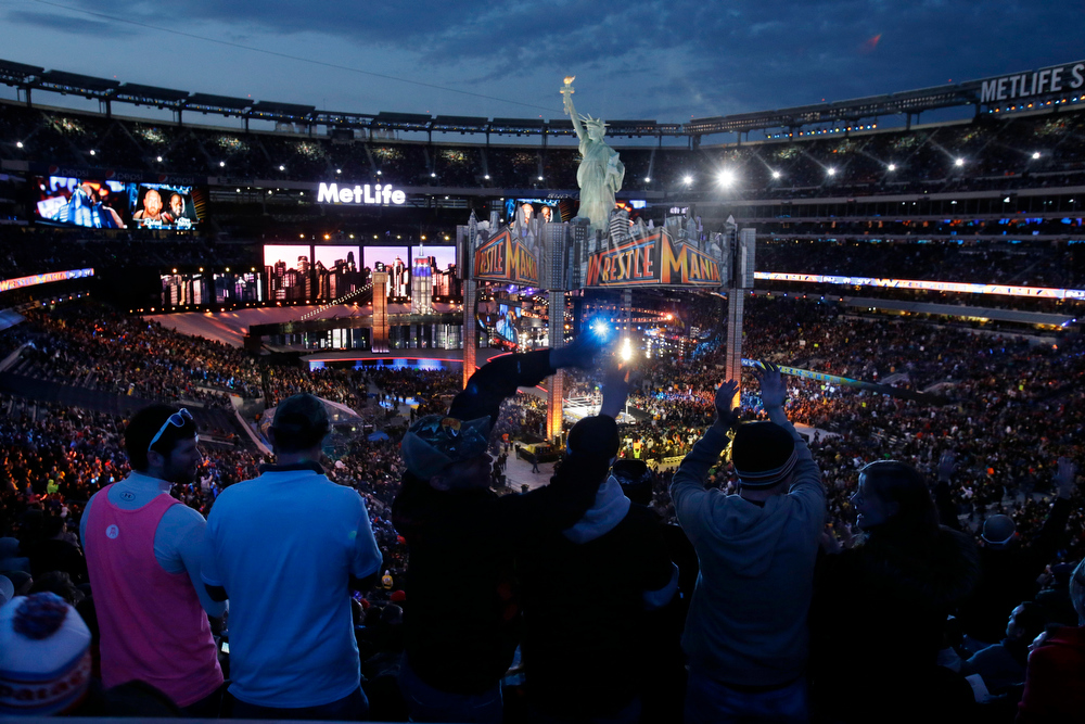 Description of . Fans watch the WWE Wrestlemania 29 wrestling event, Sunday, April 7, 2013, in East Rutherford, N.J. (AP Photo/Mel Evans)