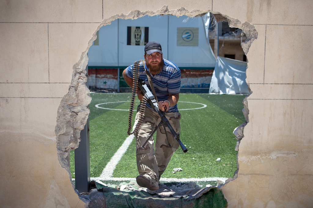 """. A rebel fighter passes through an access hole broken in the perimeter of a football pitch, close to the front line, where clashes between the rebels and pro-government troops have been taking place on the outskirts of the northern city of Aleppo, on July 4, 2013. Syria\'s President Bashar al-Assad accused the West of sending \""""takfiri terrorist groups\"""" to his country as a way to get rid of them, in an interview with a Syrian daily published. DANIEL LEAL OLIVAS/AFP/Getty Images"""