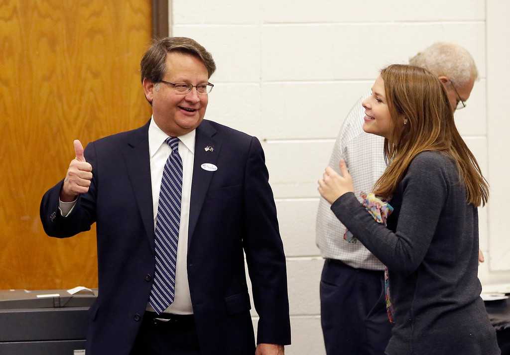 . Michigan Democratic Senate candidate Gary Peters gives a thumbs up next to his daughter Madeleine after voting in Bloomfield Hills, Mich., Tuesday, Nov. 4, 2014. Peters is running against Republican Terri Lynn Land for the seat of retiring Democrat Carl Levin. (AP Photo/Carlos Osorio)