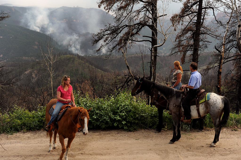 . JEFFERSON COUNTY, CO - JUNE 20:  Concerned residents Kelly Phillips, in pink, riding Tuff, on the left Craig Reisinger on his horse Indy, in blue shirt,  and Darcelle Mattson on her horse Nevada look over at the Lime Gulch Fire from Elk Ridge Road below Kuehster Road on June 20, 2013. (Their horses are all rescued BLM mustangs.)  The Lime Gulch Fire which is burning off of Foxton Road near Conifer, CO continues to burn almost next to last year\'s Lower North Fork fire on June 20, 2013.  This area along Kuehster Road is where many homes burned in the Lower North Fork Fire in March of 2012.  Photo by Helen H. Richardson/The Denver Post)
