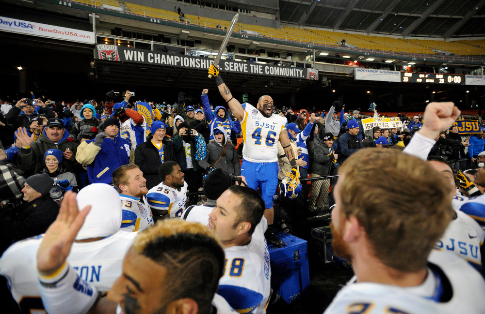 Description of . San Jose State running back Ray Rodriguez (46) hoists a sword after they defeated Bowling Green 29-20 in the NCAA college football Military Bowl, Thursday, Dec. 27, 2012, in Washington. (AP Photo/Nick Wass)