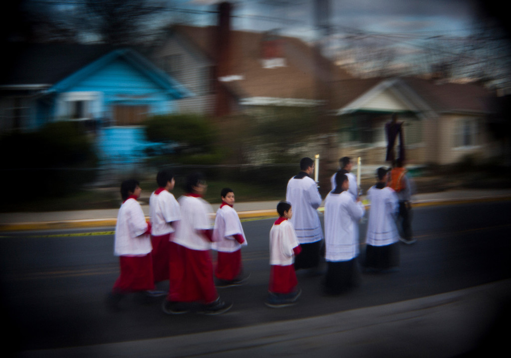 . Altar boys and priests walk through Roland Doe\'s boyhood neighborhood during a Via Crucis parade organized by the boy\'s old church, Saint James Parish, in Prince George\'s County, Maryland, USA, 29 March 2013. In 1949, a Saint James priest named Father Albert Hughes first proclaimed Roland\'s need of an exorcism. Roland, who was then Lutheran, converted to Catholicism and joined Saint James Parish.  All of the pictures for this essay were made with specialty lenses attached to a 35mm camera. EPA/JIM LO SCALZO