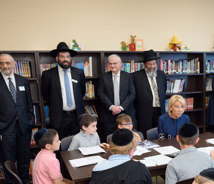 Secretary DeVos discussing poetry with fourth graders in the Willens Literacy Library at Yeshiva Darchei Torah. Standing, L-R: Rabbi Chaim Dovid Zwiebel, Rabbi Moshe Bender, Mr. Ronald Lowinger and Rabbi Yaakov Bender.