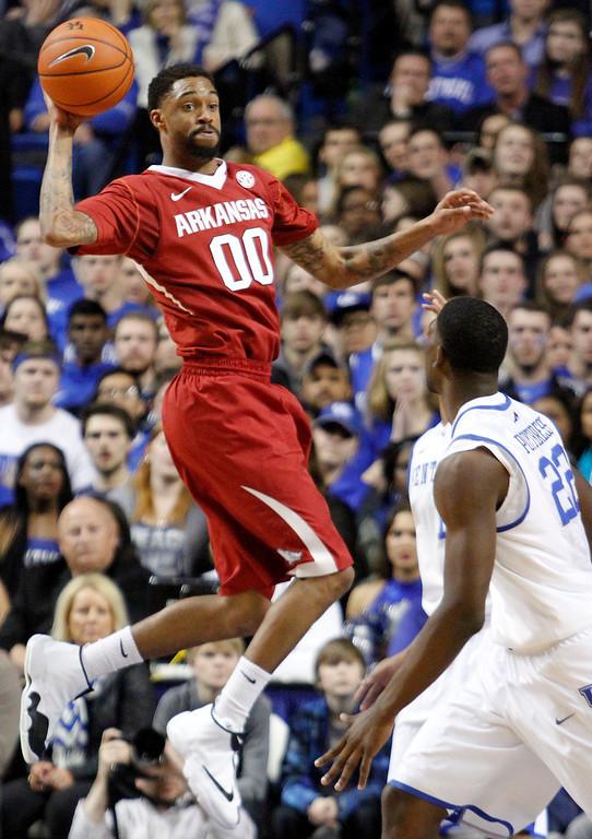 . Arkansas\' Rashad Madden looks for an open teammate as Kentucky\'s Alex Poythress (22) watches during the first half of an NCAA college basketball game Thursday, Feb. 27, 2014, in Lexington, Ky. (AP Photo/James Crisp)