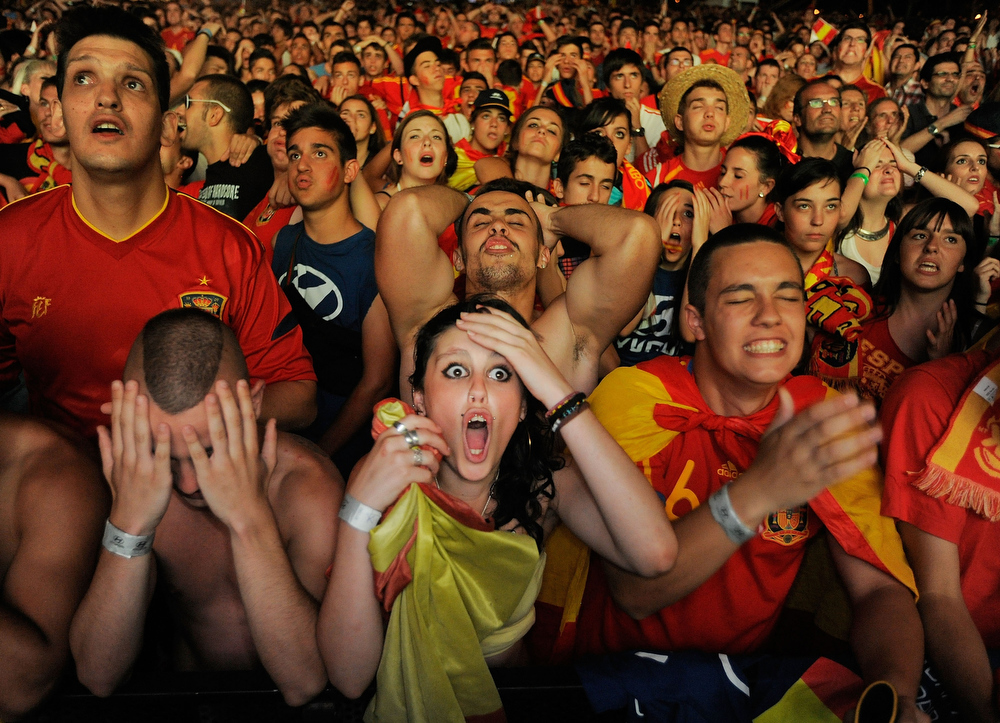 Description of . Spanish fans react while watching on a giant outdoor screen on Paseo de La Castellana street the UEFA EURO 2012 semi-final match between Spain and Portugal on June 27, 2012 in Madrid, Spain.  (Photo by Denis Doyle/Getty Images)