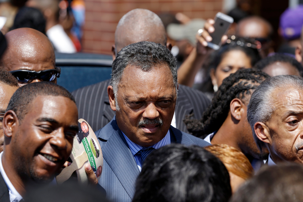 Description of . Rev. Jesse Jackson attends the funeral for Michael Brown Monday, Aug. 25, 2014, in St. Louis. Brown, a black 18-year-old who was unarmed, he was shot Aug. 9 by Officer Darren Wilson, who is white. A grand jury is considering evidence in the case and a federal investigation is also underway. (AP Photo/Jeff Roberson)