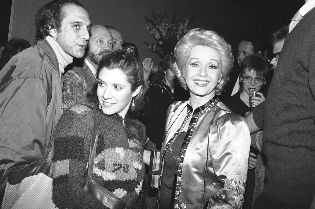 """. Actress Debbie Reynolds, right, and daughter actress Carrie Fisher have smiles for the crowd of well wishers at a party in New York, Feb. 17, 1983 marking Miss Reynolds\' return to Broadway. Miss Reynolds steps into \""""Woman of the Year\"""" which previously starred Lauren Bacall and Raquel Welch. (AP Photo/Nancy Kaye)"""