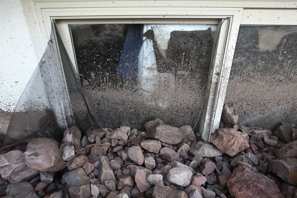 . Rocks are piled against a window where homes are covered with rocks and mud after debris flows smashed into houses as a powerful storm that has been lashing northern California moves southward on December 12, 2014 in Camarillo Springs neighborhood of Camarilla, California.  (Photo by David McNew/Getty Images)