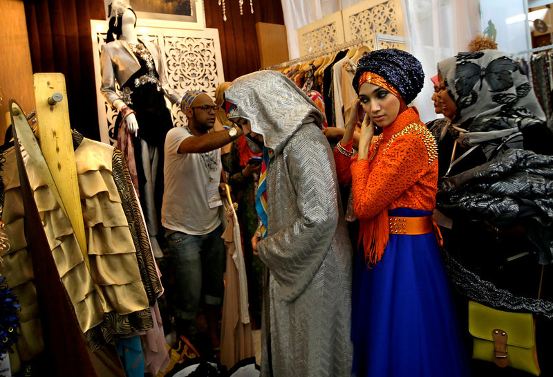. In this Thursday, May 30, 2013 photo, Indonesian Muslim women try on dresses during Islamic Fashion Fair in Jakarta, Indonesia. Indonesia is the world\'s most populous Muslim country, but most people follow a moderate form of the religion. Many women wear bright and creative headscarves along with brand-name jeans and long-sleeved fitted shirts. (AP Photo/Dita Alangkara)