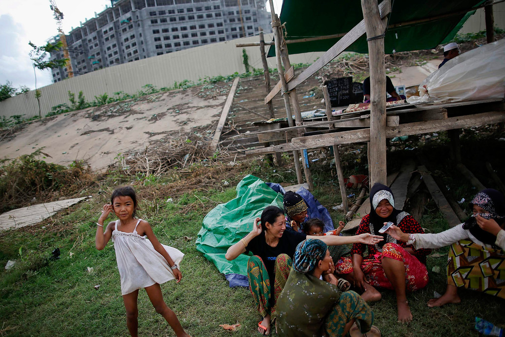 . Ethnic Cham Muslim women chat near a makeshift mosque built in front of a hotel under construction on the banks of Mekong river in Phnom Penh July 27, 2013. About 100 ethnic Cham families, made up of nomads and fishermen without houses or land who arrived at the Cambodian capital in search of better lives, live on their small boats on a peninsula where the Mekong and Tonle Sap rivers meet, just opposite the city\'s centre. The community has been forced to move several times from their locations in Phnom Penh as the land becomes more valuable. They fear that their current home, just behind a new luxurious hotel under construction at the Chroy Changva district is only temporary and that they would have to move again soon. Picture taken July 27, 2013. REUTERS/Damir Sagolj