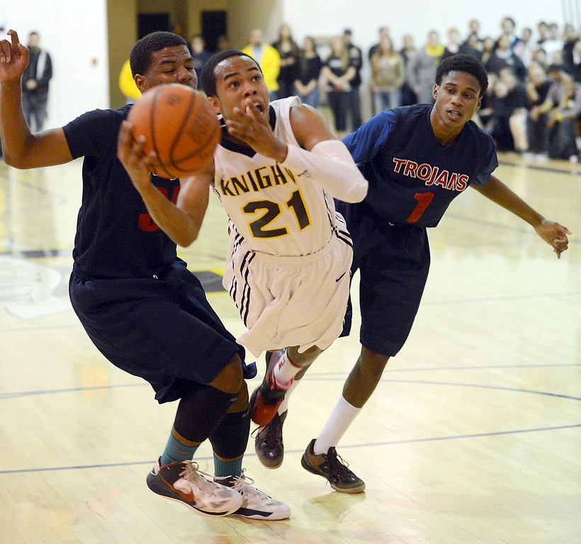 . Bishop Montgomery\'s Justin Bibbins (21) is squeezed by La Verne Lutheran\'s Joseph Rushing (35( and Tey Willians (1) in a CIF SS Division IV-AA semifinal game in Torrance Friday night. Lutheran stunned Bishop Montgomery 63-59, ending their unbeaten season. 20130222 Photo by Steve McCrank / Staff Photographer