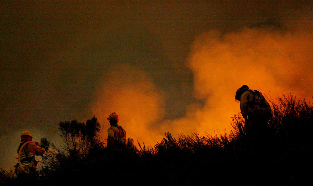 . SAN DIEGO - OCTOBER 27:  Firefighters battle a portion of the Cedar Fire October 27, 2003 near Lakeside in San Diego, California. The death toll stands at 13, with more than 1,000 homes being reduced to ashes as southern California fires continue to burn. Winds have eased a bit, but 30,000 homes remain threatened by the fires, which have charred more than 400,000 acres, according to officials. Davis, who has activated the National Guard, predicted damages will be in the billions of dollars.  (Photo by Donald Miralle/Getty Images)