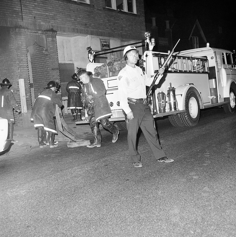 . A Cleveland policeman keeps a sharp lookout for rock-throwers as he protects city firemen fighting a small blaze near East 101st and Hough Avenue in Cleveland, Ohio, July 21, 1966. Gangs forced firemen to pull equipment back by pelting them with missiles during early stages of the race-rioting. (AP Photo)