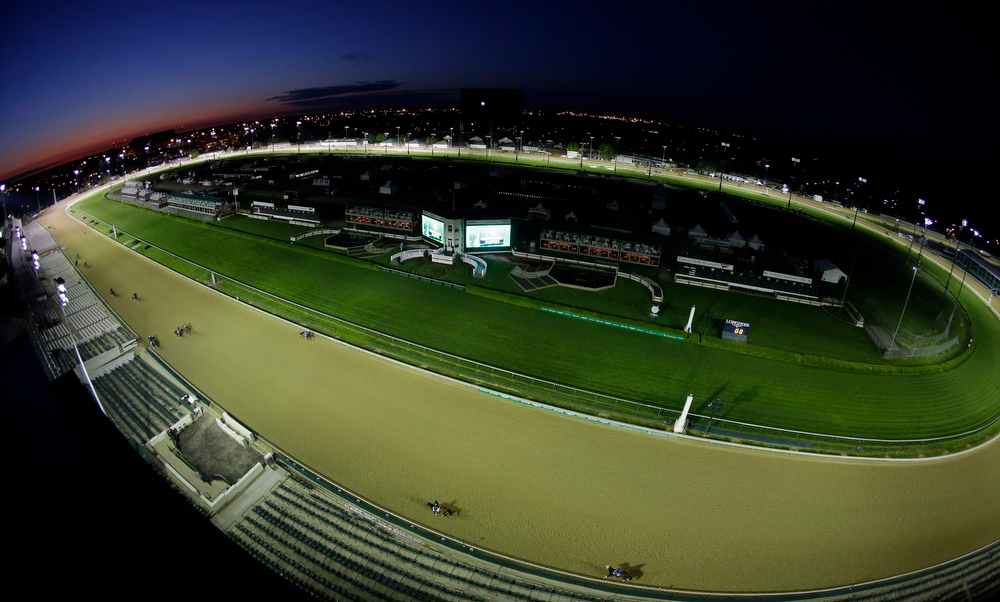 . In this image taken with a fisheye lens, horses make their way around the track for a morning workout at Churchill Downs Friday, May 2, 2014, in Louisville, Ky. (AP Photo/Charlie Riedel)