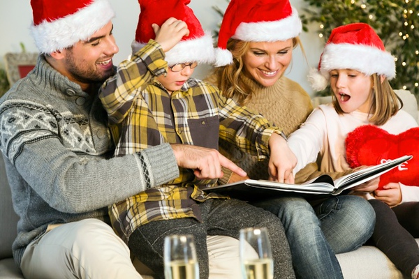 family-smiling-with-santa-claus-hats-and-looking-at-a-photo-album_23-2147580719.jpg
