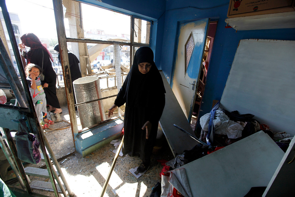 . A woman stands inside her destroyed house after a car bomb attack in the Al-Mashtal district in Baghdad March 19, 2013. REUTERS/Mohammed Ameen