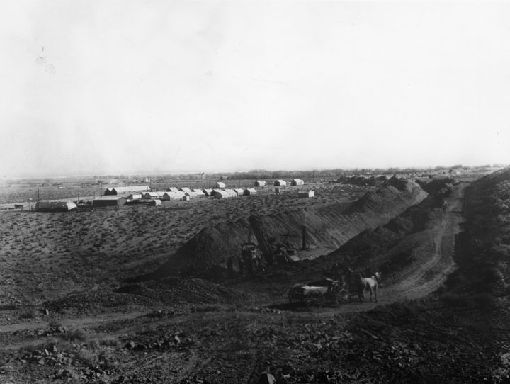 . A view of early excavation for building the L.A. Aqueduct to Owens Valley, done between 1907 and 1913. The aqueduct was considered the 2nd greatest engineering accomplishment of its age, after the Panama Canal. Here we see construction of ditches in the foreground, and the workmen\'s camp in the background. (1912)   (Los Angeles Public Library)
