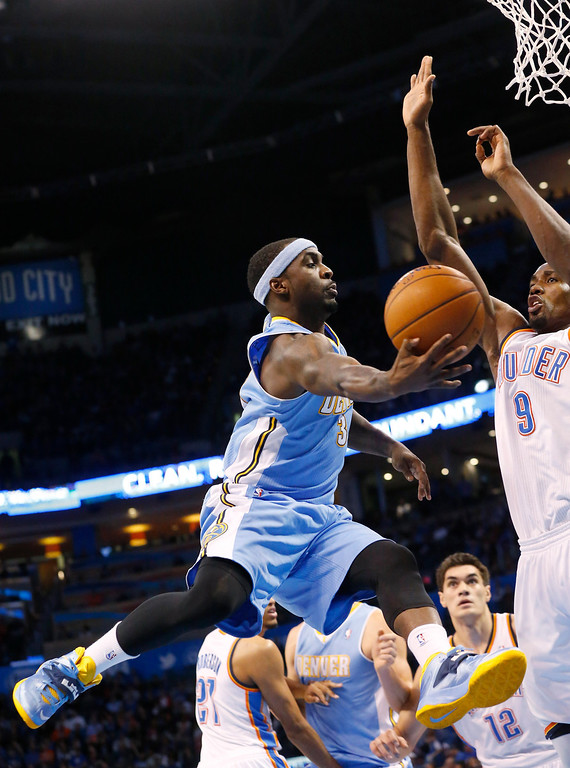 . Denver Nuggets guard Ty Lawson (3) goes up for a shot in front of Oklahoma City Thunder forward Serge Ibaka (9) in the second quarter of an NBA basketball game in Oklahoma City, Monday, March 24, 2014. (AP Photo/Sue Ogrocki)