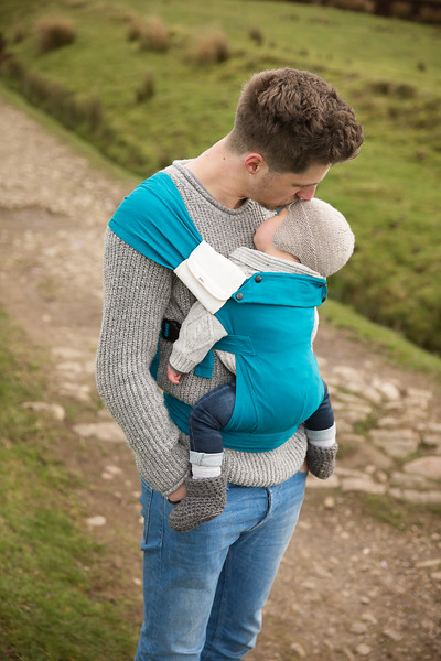 Izmi_Baby_Carrier_Cotton_Teal_Lifestyle_Front_Carry_Dad_With_Accessories_Kissing_Baby.jpg
