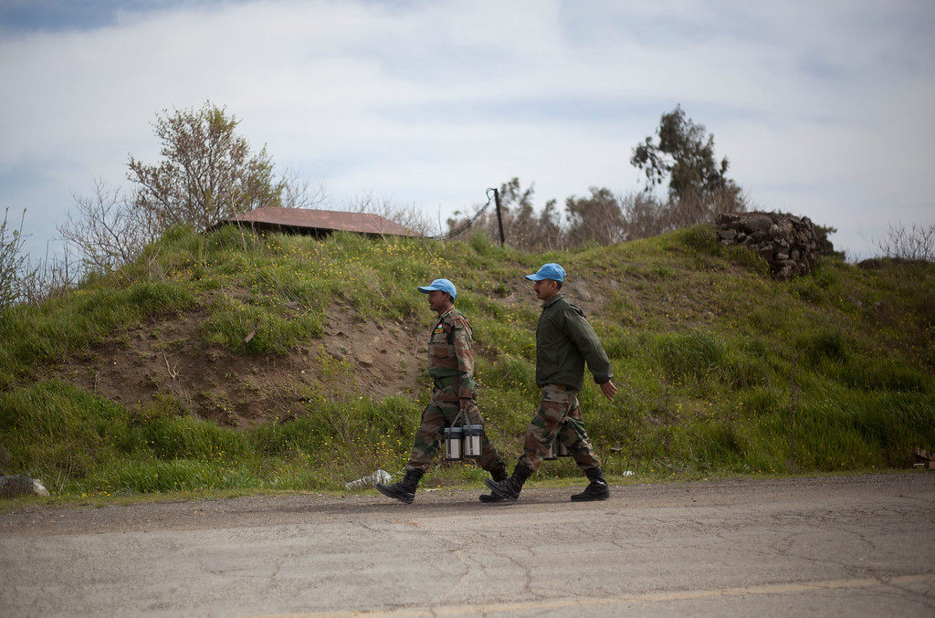. Two U.N. peacekeepers from India walk by the Quneitra Crossing between Syria and the Israeli-controlled Golan Heights, Thursday, March 7, 2013. Clashes between Syrian troops and rebel fighters flared on Thursday near an area where armed fighters linked to the opposition abducted 21 U.N. peacekeepers a day earlier. The peacekeepers are part of a force that monitors a cease-fire between Israeli and Syrian troops in the Golan Heights. Israel captured part of the territory in the 1967 Mideast war, and while the area has been peaceful for decades, Israeli officials have grown increasingly jittery as the Syrian civil war moves closer to its borders. (AP Photo/Ariel Schalit)