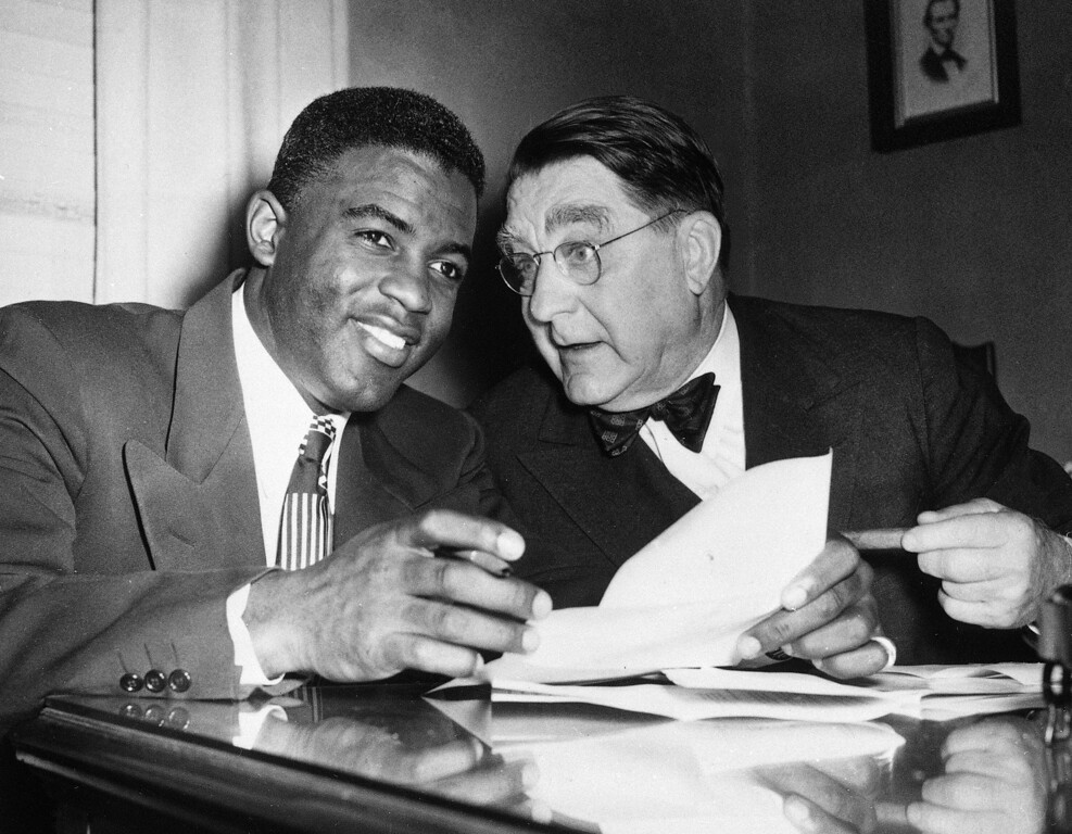 . Brooklyn Dodgers\' Jackie Robinson, left, smiles as he and Dodgers\' president Branch Rickey as they get together on Jackie\'s 1950 contract in the Dodgers\' Brooklyn offices, Jan. 24, 1950. Jackie signed the contract which is estimated at between $30,000 and $35,000. (AP Photo/Jacob Harris)