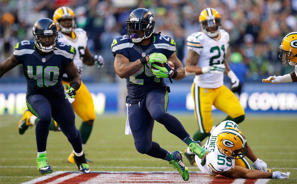 . Seattle Seahawks running back Marshawn Lynch (24) runs the ball after avoiding a tackle from Green Bay Packers inside linebacker Brad Jones, lower right, in the first half of an NFL football game, Thursday, Sept. 4, 2014, in Seattle. (AP Photo/Scott Eklund)