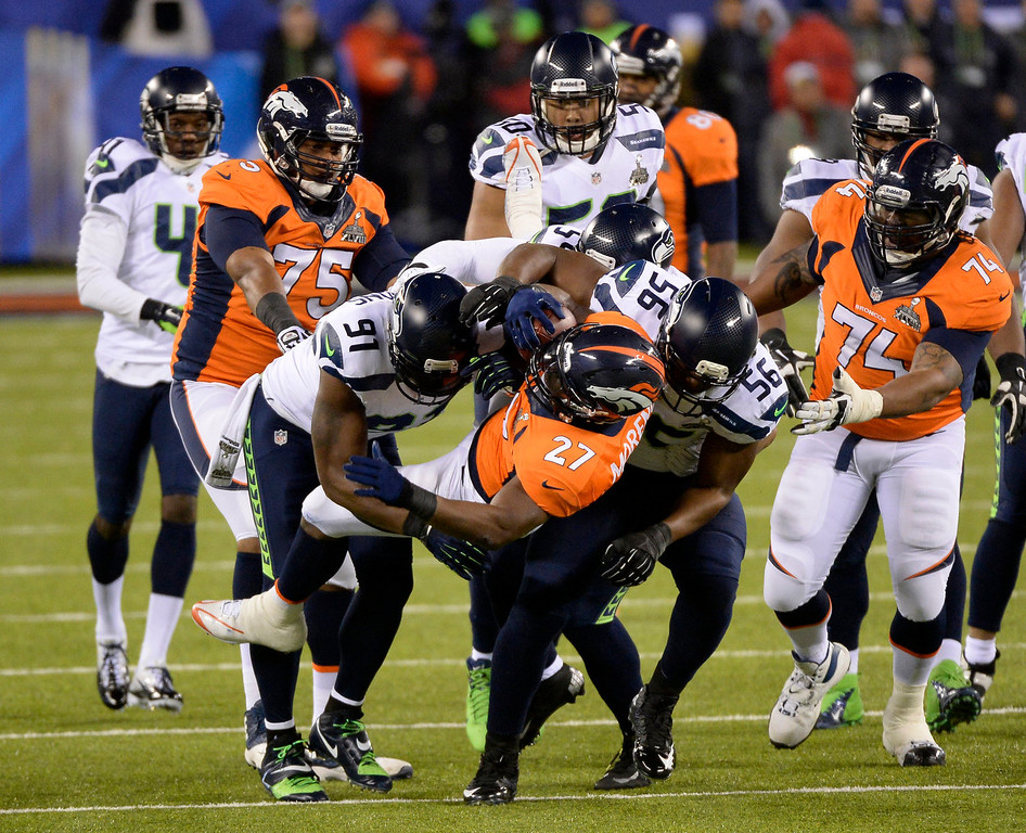 . Denver Broncos running back Knowshon Moreno (27) gets hit hard during the first quarter. The Denver Broncos vs the Seattle Seahawks in Super Bowl XLVIII at MetLife Stadium in East Rutherford, New Jersey Sunday, February 2, 2014. (Photo by AAron Ontiveroz/The Denver Post)