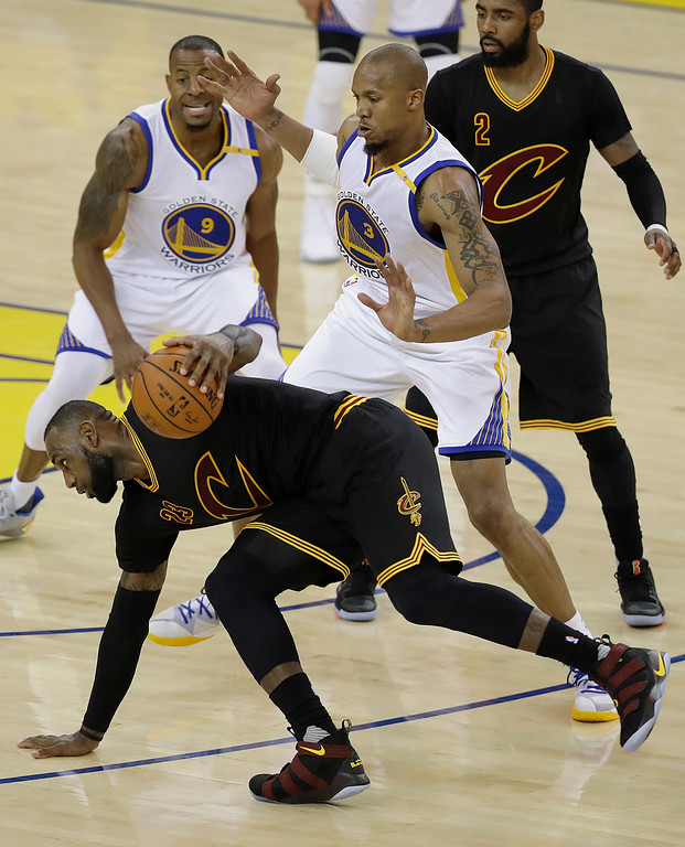 . Cleveland Cavaliers forward LeBron James, bottom, dribbles against Golden State Warriors forward Andre Iguodala (9) and forward David West (3) during the first half of Game 5 of basketball\'s NBA Finals in Oakland, Calif., Monday, June 12, 2017. (AP Photo/Marcio Jose Sanchez)