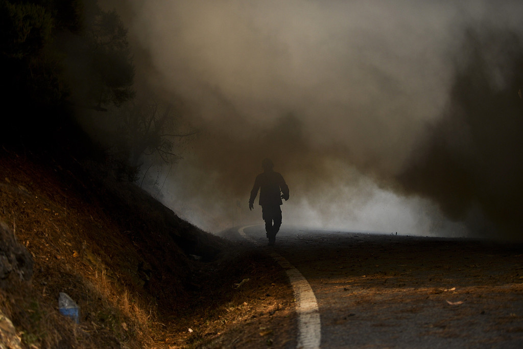 . A firefighter walks surrounded by smoke during a wildfire around Caramulo, central Portugal, on August 30, 2013.  AFP PHOTO / PATRICIA DE MELO MOREIRA/AFP/Getty Images