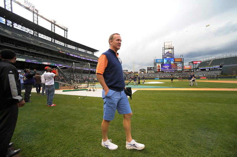 . Denver Broncos Peyton Manning walks on the grass to watch the Colorado Rockies New York Yankees batting practice May 7, 2013 at Coors Field. (Photo By John Leyba/The Denver Post)