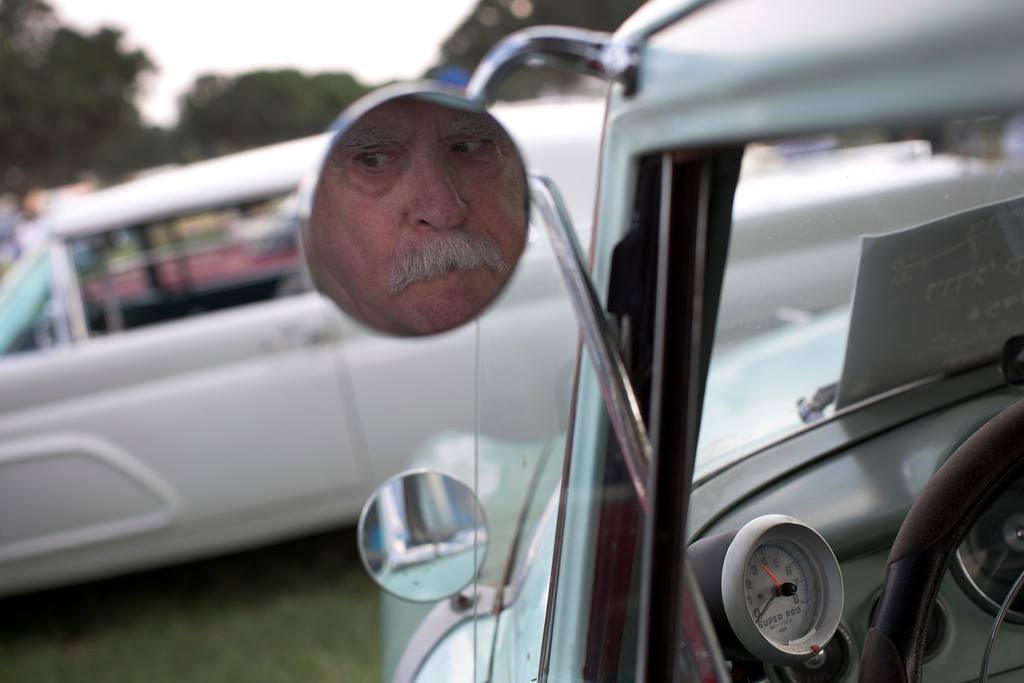 ". Zelig Rabinowitz reflected in his 1956 Dodge Coronet mirror during the 31st annual ""Five Club\"" car collectors\' meeting in Ramat Gan, Israel, Friday, Oct. 6, 2017. Each weekend, at Israeli gas stations and parking lots and parks, car collectors gather with their beauties _ and take a step back in time. (AP Photo/Oded Balilty)"