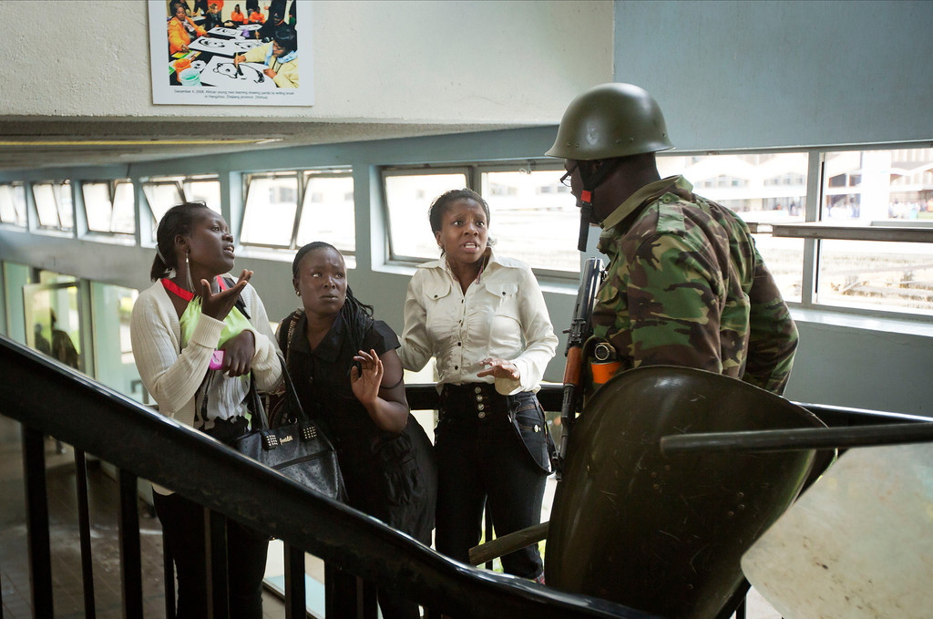 . Kenyan female students plead their innocence and beg not to be beaten by a riot policeman as they leave from a tear-gas-filled building inside Nairobi University\'s main campus in downtown Nairobi, Kenya Tuesday, May 20, 2014. Kenyan university students on Tuesday carried out demonstrations over a proposed increase in student fees, but the protests quickly turned into hours of running battles between students throwing rocks and security forces firing tear gas, before riot police chased the students inside their campus and cornered them in a building into which they fired dozens of tear gas grenades and for a while prevented anyone from leaving. (AP Photo/Ben Curtis)