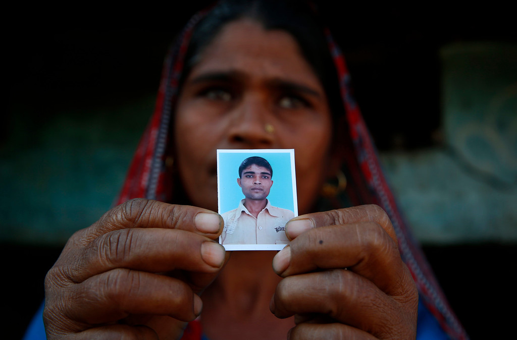 . In this Wednesday, Feb. 12, 2014 photo, Taravati, who uses only one name, shows a photograph of her son Shiv Kumar Singh, a daily wage laborer, who was killed by a tiger at Maniawala, in northern India. The tiger that killed Singh on Jan. 10 has killed at least nine people so far traveling over 120 miles of villages, small towns and even a highway, spreading fear amongst the villagers many of whom are either farmers or laborers working the the large swathes of sugarcane fields which need harvesting now. (AP Photo/Saurabh Das)