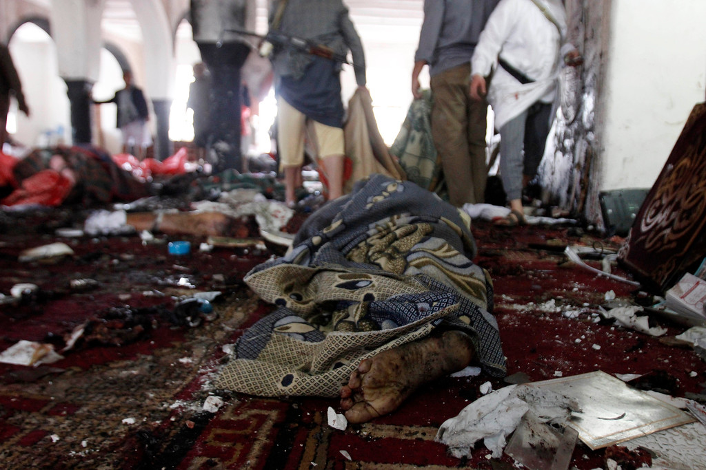 . The victim of a suicide attack during the noon prayer is covered in a blanket in a mosque in Sanaa, Yemen, Friday, March 20, 2015. Triple suicide bombers hit a pair of mosques crowded with worshippers in the Yemeni capital, Sanaa, on Friday, causing heavy casualties, according to witnesses. The attackers targeted mosques frequented by Shiite rebels, who have controlled the capital since September. (AP Photo/Hani Mohammed)
