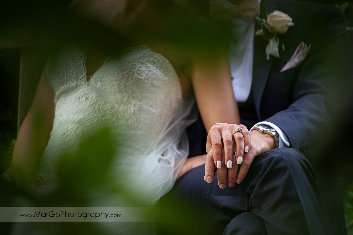 wedding rings on hands of bride and groom sitting in Piedmont Park