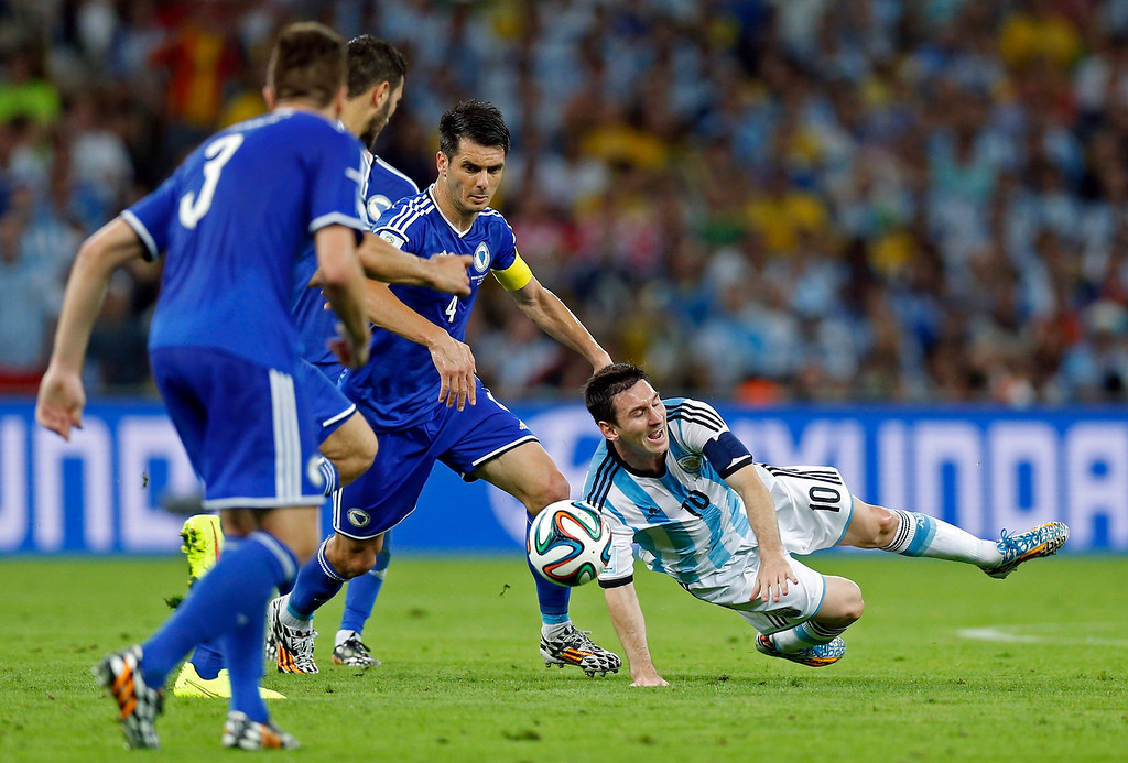 . Argentina\'s Lionel Messi falls to the pitch after being fouled during the group F World Cup soccer match between Argentina and Bosnia at the Maracana Stadium in Rio de Janeiro, Brazil, Sunday, June 15, 2014.    (AP Photo/Victor R. Caivano)