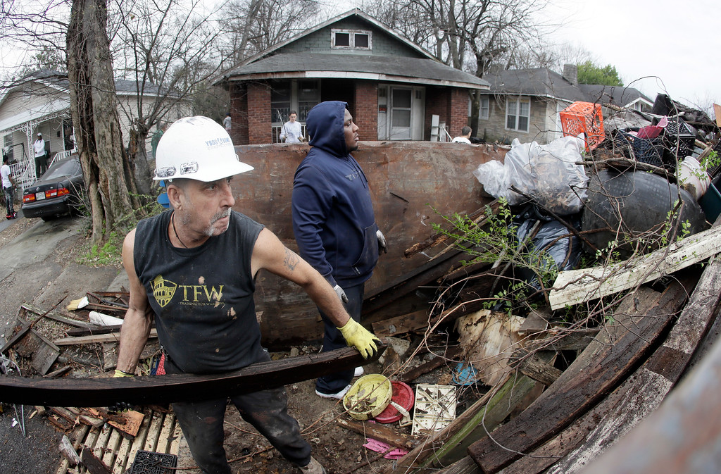 . Martin Lleras, left, and Joshua Cleaves place debris in a dumpster as a vacant house and yard, top center, are cleared of trash on  Martin Luther King Jr. Day, Monday, Jan. 16, 2017, in Memphis, Tenn. Residents of the city where civil rights leader the Rev. Martin Luther King Jr. was killed are honoring his legacy with neighborhood clean-up events and a daylong celebration at the National Civil Rights Museum. (AP Photo/Mark Humphrey)